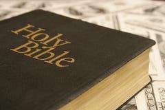 Biblia santa en fondo del dinero Imagenes de archivo