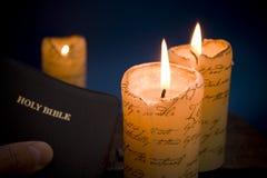 Biblia santa por luz de una vela imagen de archivo