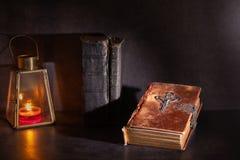 Biblia vieja en una tabla con la luz de la vela fotos de archivo
