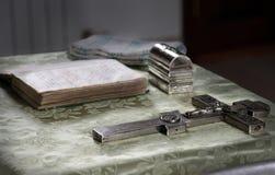 Biblia y cruz en la tabla del sacerdote Imagen de archivo libre de regalías