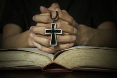 Biblia y manos que sostienen un rosario Fotos de archivo libres de regalías