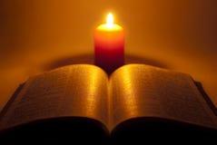 Biblia y vela de la noche. Fotos de archivo