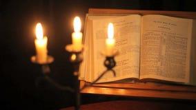Biblia y velas de la cacerola de foco del estante almacen de metraje de vídeo