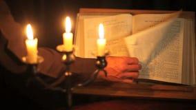 Biblia y velas de vuelta de la página almacen de video