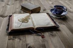 Biblias abiertas y cerradas con la taza de té Fotografía de archivo
