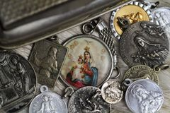 Biblical figures pendants. Necklace vintage old zilver glass bible christ maria jesus religion catholic royalty free stock images