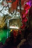 Biblical fresco on the wall of grotto. Biblical fresco on the wall of artificial grotto with greenish water and red lit ceiling in museum Stock Images
