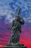 Biblical scene. Passion of the Christ on Good Friday, Jesus Christ carrying his cross on Calvary. Statue of Christ on dramatic sky in the purple rays of Royalty Free Stock Images