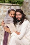 Jesus playing with a little girl. Biblical scene when Jesus says, let the little children come to me, blessing a little girl. Historical reenactment at an old Royalty Free Stock Photos