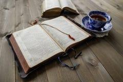 Biblie i filiżanka herbata na drewno stole Zdjęcie Royalty Free