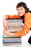 Bibliophile. Happy schoolboy sitting with a stack of books. Isolated over white stock photo