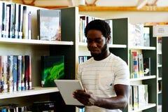 Bibliotecário que verifica o inventário na tabuleta foto de stock