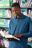Biblioteca adolescente masculina de Reading Book In del estudiante Imagenes de archivo