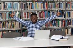 Biblioteca africana feliz de With Laptop In del estudiante masculino fotografía de archivo libre de regalías