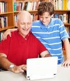 Biblioteca - computando com paizinho Imagem de Stock Royalty Free