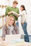 Biblioteca da High School - estudante feliz com portátil imagens de stock royalty free