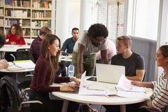 Biblioteca da universidade ocupada com estudantes e tutor imagem de stock