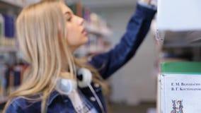 Biblioteca de faculdade Estudante Girl Looking Books em estantes filme