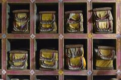 Biblioteca de libros tibetanos: manuscritos tibetanos antiguos envueltos en los paños sacros brillantes, mentira en armario espec Fotografía de archivo libre de regalías