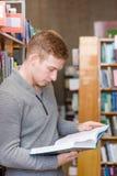 Biblioteca de Reading Book In del estudiante masculino Foto de archivo libre de regalías
