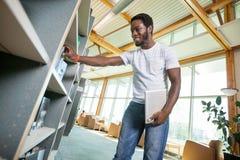 Biblioteca de Selecting Book In del estudiante Fotografía de archivo libre de regalías