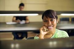 Biblioteca de universidad y estudiante, mujer negra que mira el camer Fotografía de archivo libre de regalías