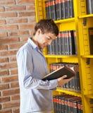 Biblioteca di istituto universitario di Reading Book In dello studente Immagine Stock Libera da Diritti