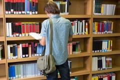 Biblioteca di Reading Book In dello studente Immagine Stock