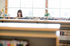 Biblioteca di Selecting Book In dello studente Immagini Stock