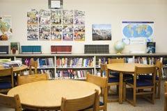 Biblioteca escolar alta com tabelas e as cadeiras arranjadas Fotografia de Stock Royalty Free