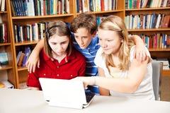 Biblioteca - estudiantes en el ordenador Imágenes de archivo libres de regalías