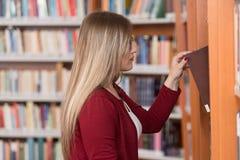 Biblioteca felice di With Book In della studentessa Fotografie Stock Libere da Diritti