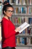 Biblioteca felice di With Book In della studentessa Immagini Stock