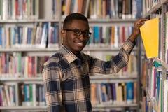 Biblioteca felice di With Book In dello studente maschio Fotografie Stock