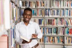 Biblioteca feliz de With Book In del estudiante masculino Foto de archivo libre de regalías