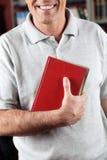 Biblioteca maschio di Holding Book In del bibliotecario Fotografie Stock Libere da Diritti