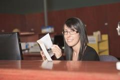 Bibliotecario femminile sorridente che tiene una condizione del libro Immagini Stock