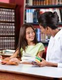 Bibliotecario And Schoolgirl Looking ad a vicenda dentro Immagine Stock Libera da Diritti