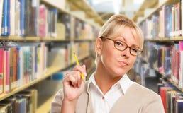 Bibliotecario, studente o insegnante biondo con la matita in biblioteca Immagine Stock