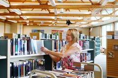 Bibliotekarie som byter ut böcker på hyllor Royaltyfri Fotografi