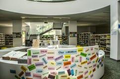 Bibliothèque avec une table ovale pour remplir la fonction, les noms des étudiants sur le conseil, bibliothèques entre les colonn photos stock