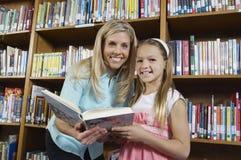 Bibliothèque de Holding Book In de fille et de professeur Image stock