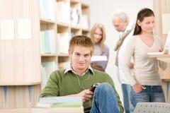 Bibliothèque de lycée - étudiant avec des écouteurs Image stock