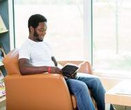 Bibliothèque de Reading Book In d'étudiant Photos stock