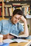 Bibliothèque de Reading Book In d'étudiant masculin Image libre de droits