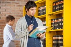 Bibliothèque universitaire de Reading Book In d'étudiant masculin Images stock