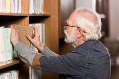 bibliothécaire gris de cheveux prenant le livre photos stock