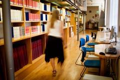 Bibliothecaris die onderaan een bibliotheekdoorgang loopt stock foto
