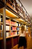 Bibliothecaris die onderaan een bibliotheekdoorgang loopt stock afbeeldingen