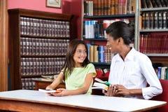 Bibliothecaris Looking At Schoolgirl terwijl het Zitten met royalty-vrije stock afbeelding